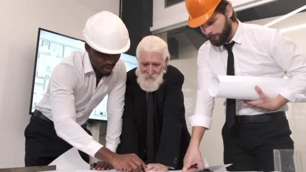 Skupina inženýrů se dívá na plán výstavby na stole