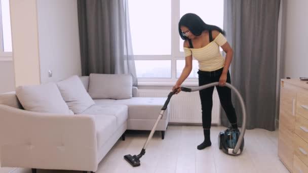 Fröhliche afrikanisch-amerikanische Frau staubsaugt Boden in modernem Haus