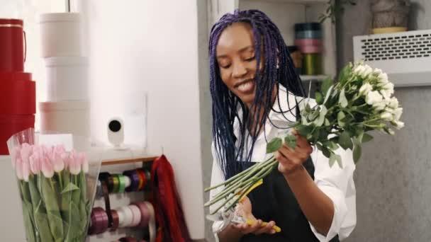 Žena květinářství v brýlích aranžování kytice a řezání růží se střihačem v květinářství