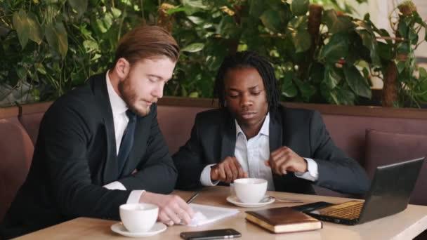 Konzentrierter Geschäftsmann im Gespräch mit Partner und Weiterverkauf von Papieren im Restaurant