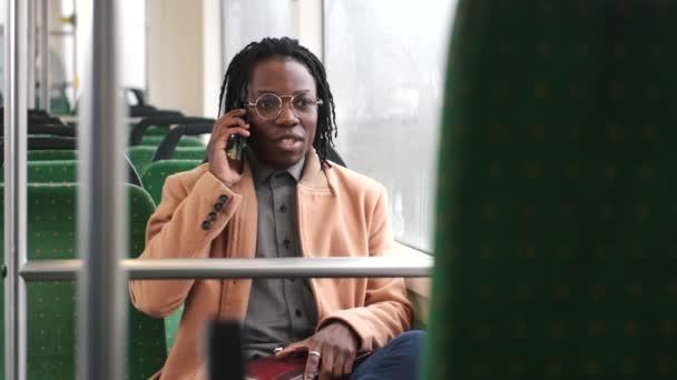 Afričan Američan v kadual oblečení používat telefon ve veřejné dopravě