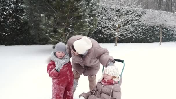 Junge glückliche Mutter und ihre Tochter genießen eine Schlittenfahrt in einem schönen verschneiten Hinterhof