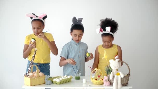 Africké americké děti v legrační králík uši omalovánky vejce na Velikonoce