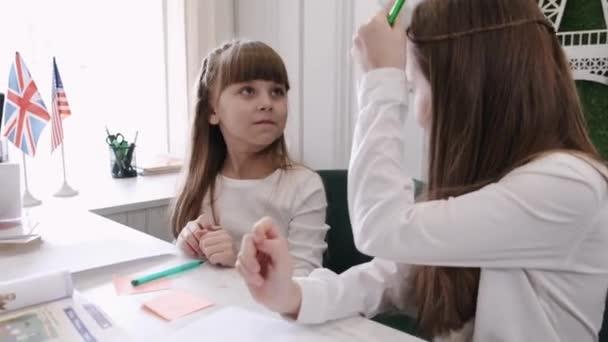A tanár két iskoláslányt tanít az osztályteremben.