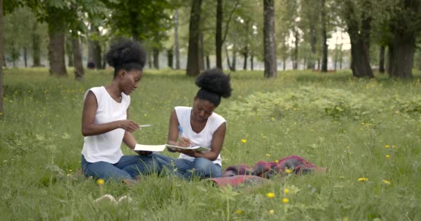two pretty young girls students sitting on a grass at the campus