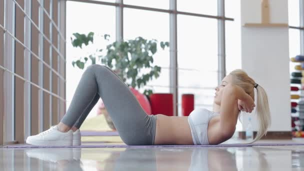 Beautiful blonde doing gym exercises