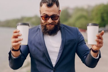 bearded man carrying coffee