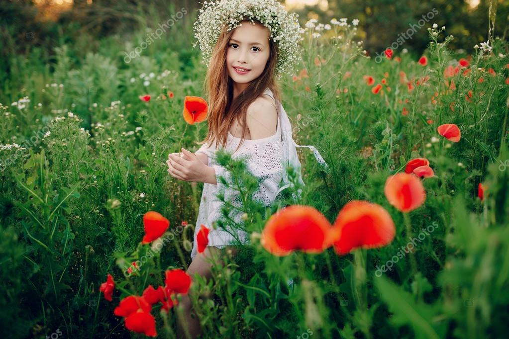 beautiful little girl posing   skirt in  wreath of poppies