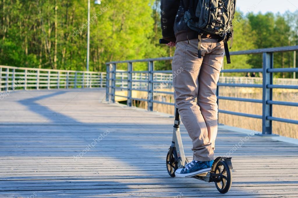 Молодой человек в повседневной одежде на кик скутере в ...