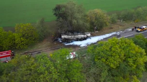 Nehoda na dálnici. Náklaďák se přestal ovládat, odletěl ze silnice, narazil do stromu a vznítil se. Letecký pohled na nehodu na dálnici. 911. Záchranáři pracují.