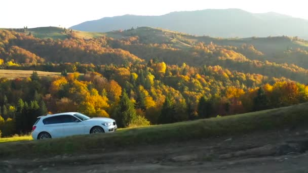 Top cinematic aerial view of the sport car which drives up the hill in the Carpathian Mountains. Ukraine. Ukrainian wild nature. Autumn season. Traveling around country. Car trip with friends. Active lifestyle holidays. Amazing autumn colors