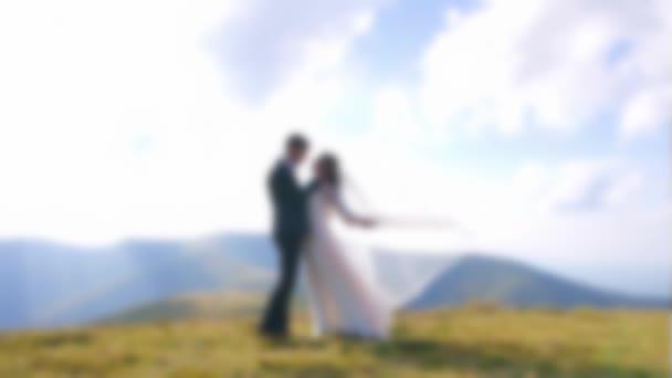 Homályos videó. Gyönyörű házaspár áll a hegycsúcson. Kedves friss házasok ölelkeznek és csókolóznak a természetben. A vőlegény és a menyasszony együtt. Romantikus naplemente, lassított felvétel. Fókuszon kívüli videó.
