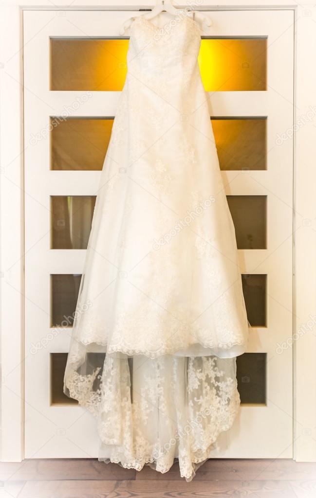 vestido de boda colgado en una puerta de luz de la habitación