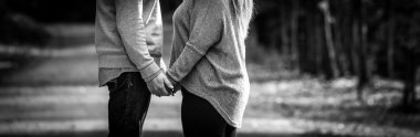 Young couple facing each other while holding hands, black and white, expressing love,