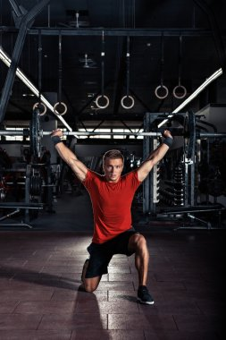 Young man  with barbell in gym