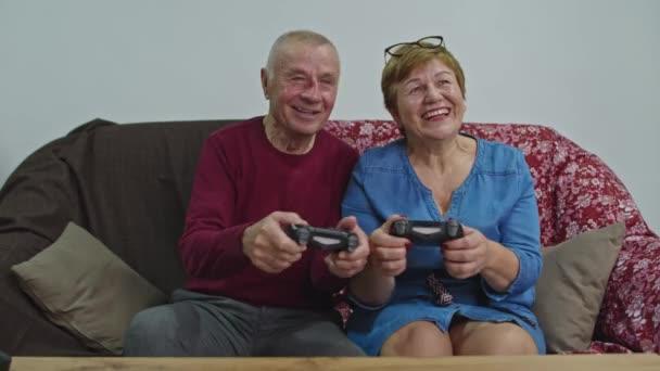 Idősebb pár játszadozik joysticksszal. A házastárs veszít és ideges lesz..