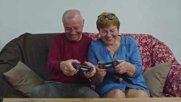 Az idősebb pár otthon játszik, a kanapén ülnek egy videojátékban. A karantén ideje.