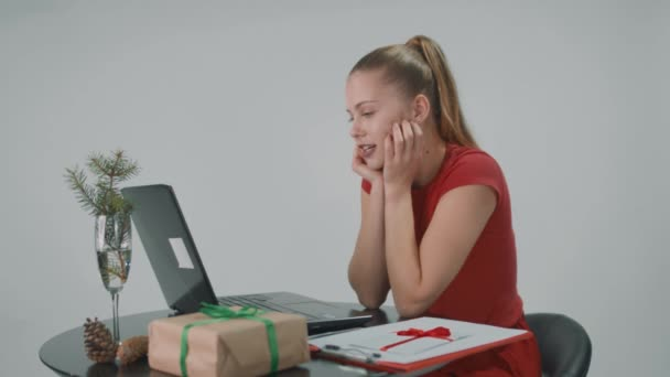 Young pretty woman in red dress is sitting on a chair in front of computer in the office and talking to sombody online.