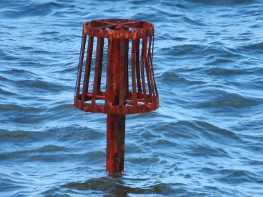 red bell buoy close up sunk in sea