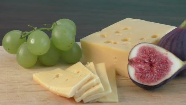 Žlutý sýr a čerstvé fíky na dřevěné prkénko