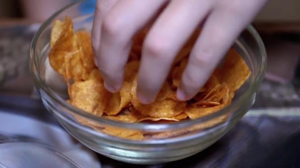 Kid Hand elviszi Crispy-t, az Arany Krumpli Chips-et a tányérról. Ártalmas élelmiszer.