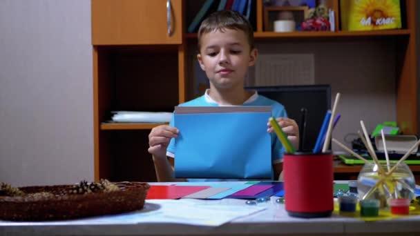 Seriózní chlapec v modrém tričku zvedá ruce a ukazuje modré na barevném papíru
