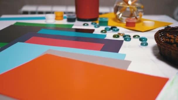 Na stole je barevná paleta papíru. Duhová kompozice. Tvůrčí myšlení