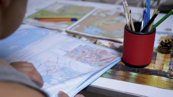 Koncentrált, okos iskolás fiú térképet, földrajzot tanul. Online Otthoni képzés.