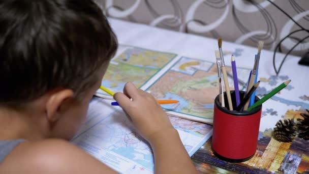 Az iskolás fiú térképet tanul tollal és ceruzával a kezében. Online otthoni oktatás