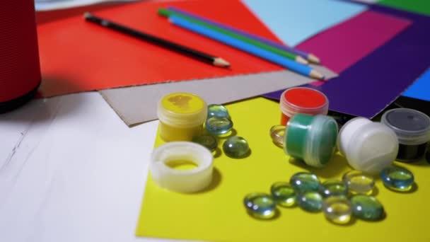 Na stole jsou náhodně uspořádané barvy, tužky, štětce, barevný papír