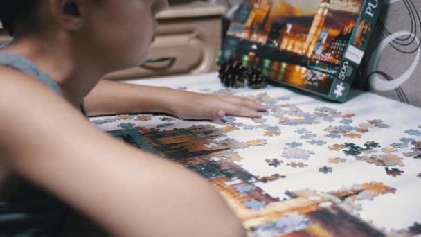 Teen sbírat puzzle na stole. Koncept vývoje dítěte. Hry pro rychlé vtipy