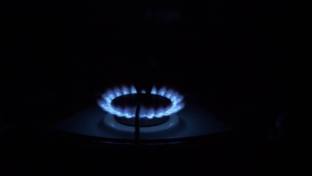 Gasbrenner an, mit blauer Flamme glühend, nachts in der Küche. Nahaufnahme
