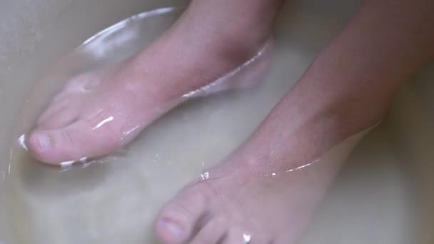 Pařené dětské nohy koupající se v horké vodě v umyvadle. Mytí špinavých nohou. 4K