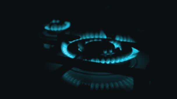 Schalten Sie in der Nacht in der Küche Gasbrenner ein, die mit einer blauen Flamme lodern. Nahaufnahme