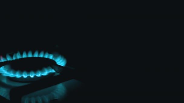 Schalten Sie nachts in der Küche Gasbrenner ein, die mit blauer Flamme lodern. Schließen