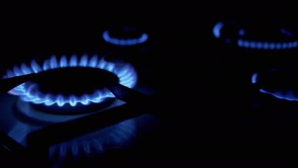 Vier mit blauer Flamme glühende Gasbrenner in der Nacht in der Küche. Nahaufnahme