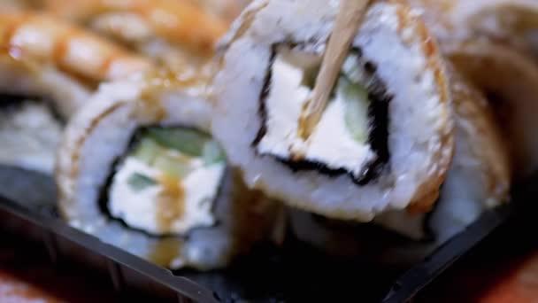 Sushi Master s bambusovými tyčinkami roztahuje sushi rolky do plastové krabice. Přiblížení
