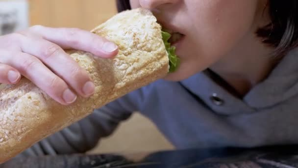Hladová žena jí předkrm šťavnatý americký hot dog s klobásami v jídelně. 4K