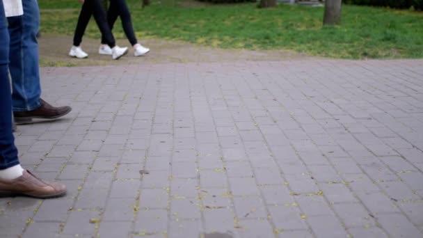 Nohy lidí, kolemjdoucí, procházka po dlažebních plátech v parku. Zpomalený pohyb