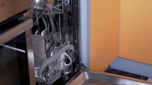 Mensch stellt schmutziges ungewaschenes Geschirr in die Regale einer Spülmaschine. Zoom