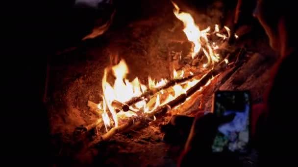 Hungrige Touristen grillen Würstchen auf Holzspießen, sitzen am nächtlichen Lagerfeuer. 4K