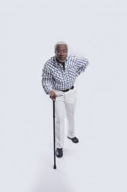 Aged man walks with cane