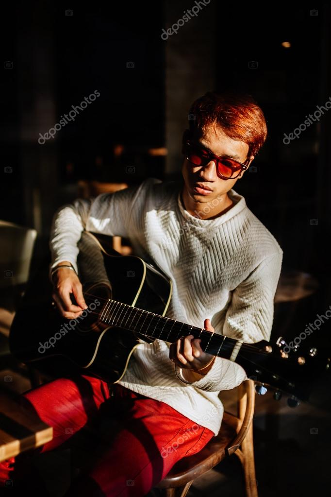 3326c64aa4 Asian handsome fashion guitarist artist man play acoustic guitar in cafe.  Shot through the window — Photo by ...