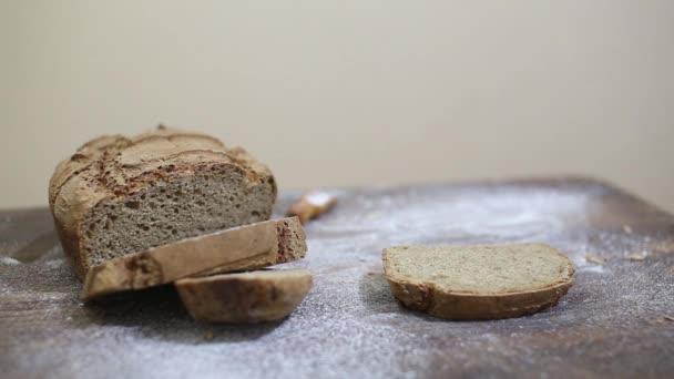 Baker, přilévá olej na kus čerstvě upečený domácí organické kváskový žitný chléb