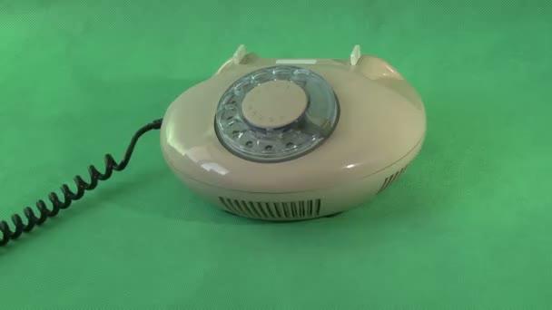 Starý telefon na zeleném pozadí
