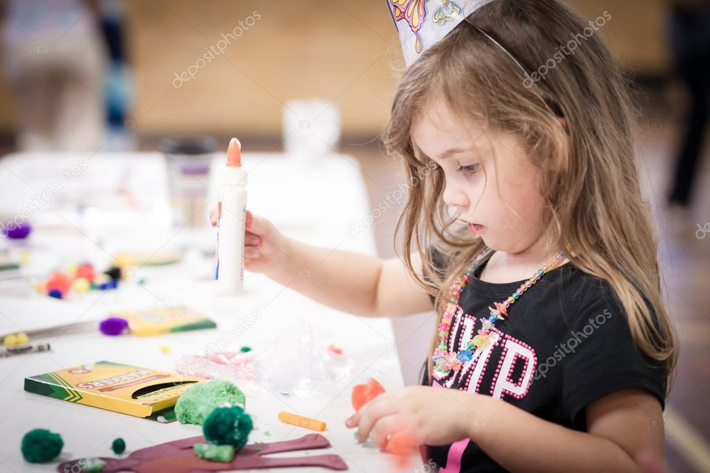 little girl making handcraft at a table