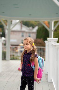 little girl with pony tails and backpack going to school