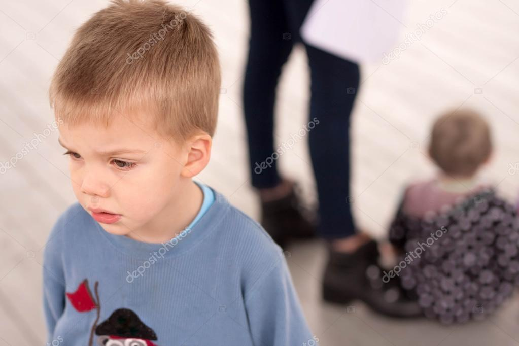 sad boy jealous about being neglected by his mother or caregiver who is giving attention to another child