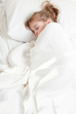 a little girl with pony tail sleeping covered with blanket