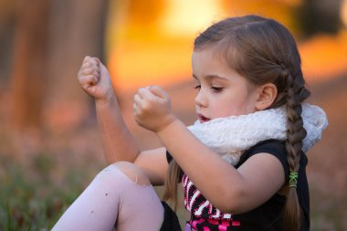 a little girl is trying to fix her hole in her tights